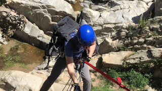 Andrew rappelling down Ortega Falls route