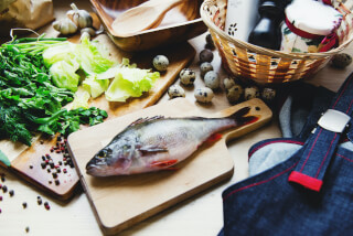 raw-fish-on-cutting-board-with-lettuce-in-kitchen