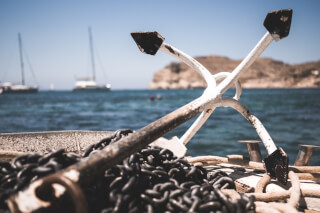 white-and-black-anchor-with-chain-at-daytime