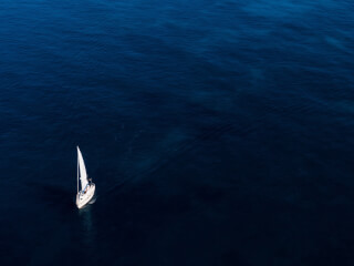 white-boat-sailing-on-body-of-water