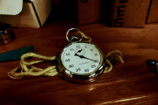 white-pocket-watch-with-gold-colored-frame-on-brown-wooden
